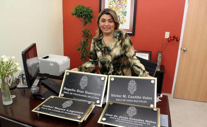 La directora de la Facultad de Psicología, Lorena Gamboa Ancona, posa con las placas de las nuevas instalaciones. (Milenio Novedades)
