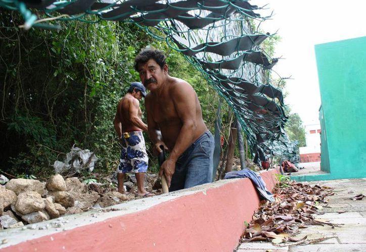 Empleados del hotel Paradisus construyen una barda para proteger sus predios, en la colonia Colosio de Playa del Carmen. (Octavio Martínez/SIPSE)