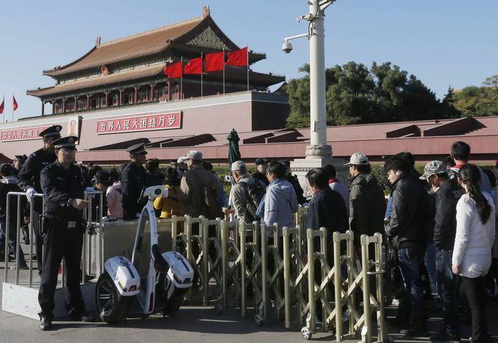 Un policía chino vigila la fila de visitantes que acceden a la Ciudad Prohibida, en la plaza de Tiananmen. (Archivo/EFE)