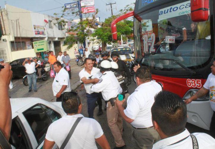 El conflicto entre taxistas y el conductor de un autobús de la zona hotelera terminó con intervención de la Policía. (Sergio Orozco/SIPSE)