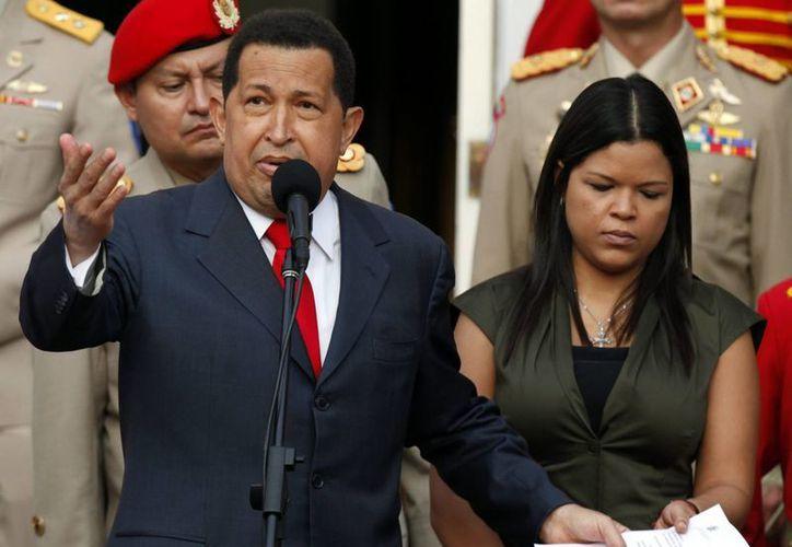 El extinto mandatario, en una de sus últimas apariciones públicas, acompañado de su hija María Gabriela. (EFE)