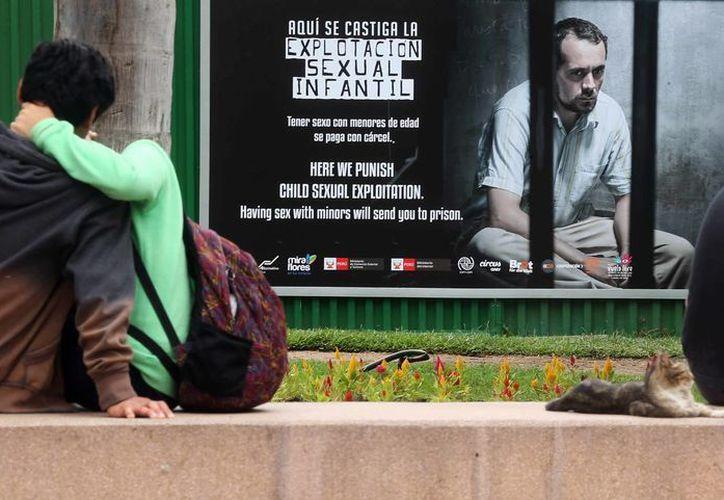 Una pareja se besa junto una imagen contra la explotación sexual infantil. (Archivo/EFE)
