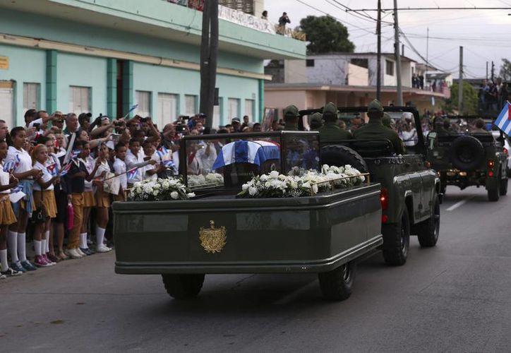 Cubanos saludan al paso de la caravana con las cenizas del fallecido líder de la revolución cubana, Fidel Castro, en Santa Clara. (EFE)