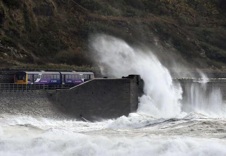 Un tren viaja por una ruta costera cerca de Whitehaven, en el noroeste de Inglaterra, mientras oleaje desatado por los restos del hucarán Gonzalo golpean la costa. (Agencias)