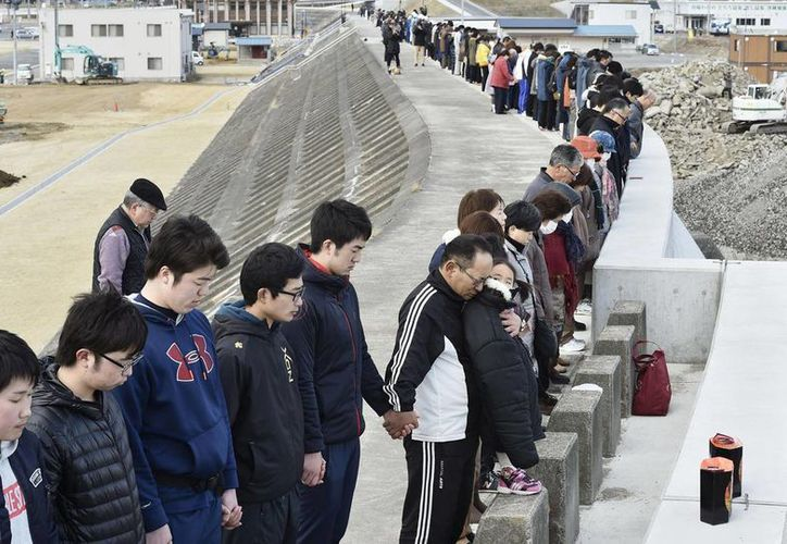 Japoneses recuerdan a las victimas del terremoto y posterior tsunami que devastó parte de ese país hace cinco años. (AP)