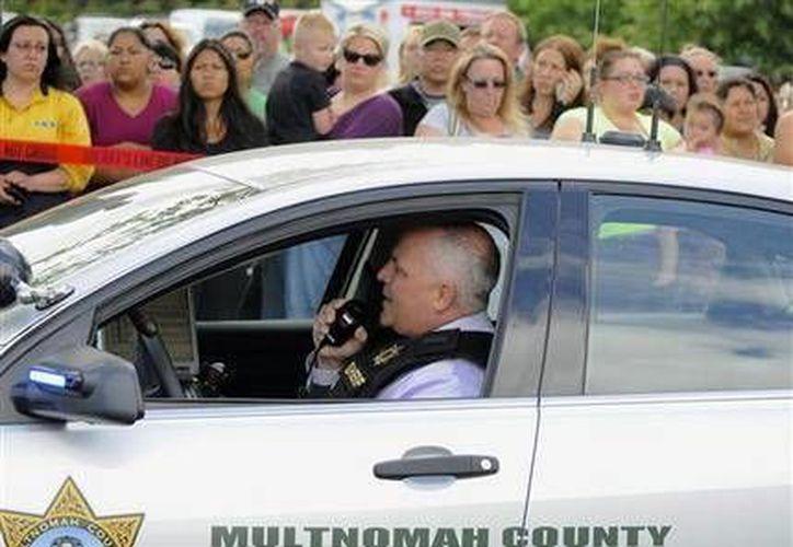 Un agente habla por la radio mientras padres y madres aguardan a sus hijos en el estacionamiento de un centro comercial en Wood Violage, Oregon, después de un tiroteo en la secundaria Reinolds en Troutdale. (Agencias)