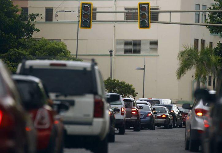 Fotografía de una larga fila de vehículos en un semáforo apagado debido a un apagón general, este 21 de septiembre 2016, en San Juan, Puerto Rico. (EFE)