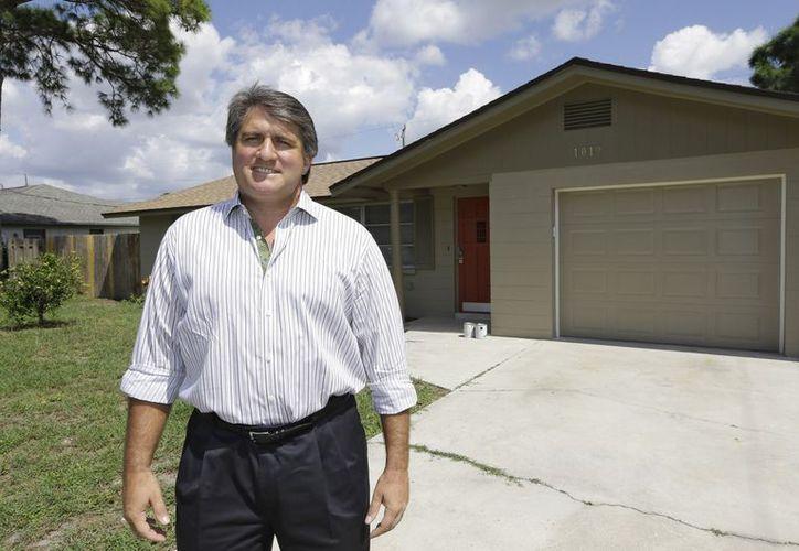 Andrew Neitlich posa frente a una de las casas que compró como inversión en Venice, Florida. (Agencias)