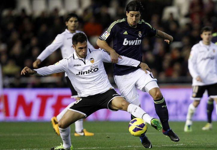 Sami Khedira del Real Madrid (d) en duelo por el balón con Víctor Ruiz del Valencia, en el partido efectuado en el estadio de Mestalla. (Agencias)