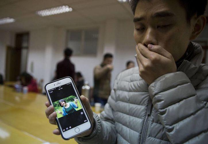Zhao Weiwei muestra la fotografía de su novia Pan Haiqin, quien murió en una estampida humana en Shanghai, China. (Agencias)