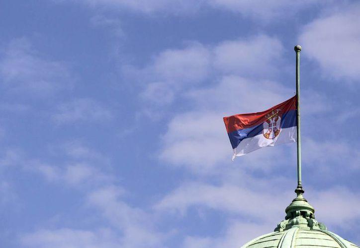 La bandera de Serbia ondea a media asta en el Parlamento de ese país como señal de luto por la matanza de 13 personas en la villa Velika Ivanca.  (Agencias)