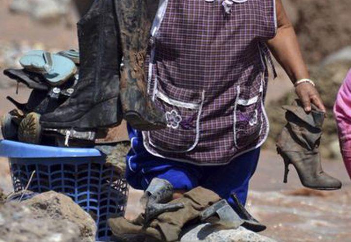 Una mujer trata de rescatar lo más posible después de que su casa se vio afectada por las inundaciones durante la Tormenta Tropical Manuel en Chilpancingo. (Agencias)