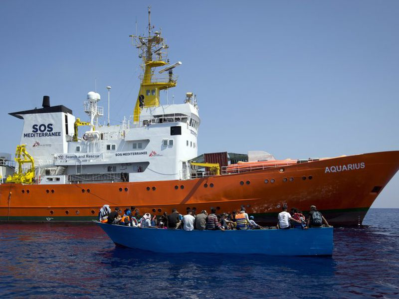 African migrants float on a wooden boat next to a rescue ship, in the Mediterranean Sea, north of Libyan coast. (AP)