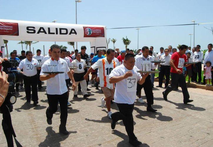 La dinámica del evento consistía en llevar en una charola dos vasos con agua, y recorrer poco más de 500 metros. (Tomás Álvarez/SIPSE)