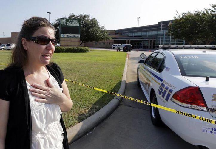 Una mujer espera a su hijo afuera del colegio donde se registró el incidente. (Agencias)