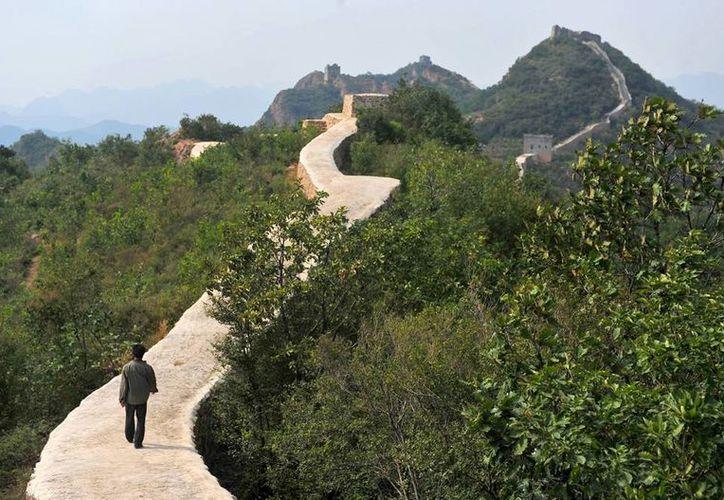 Una persona caminan por una sección restaurada de la Gran Muralla China, en Suizhong. (Chinatopix via AP)