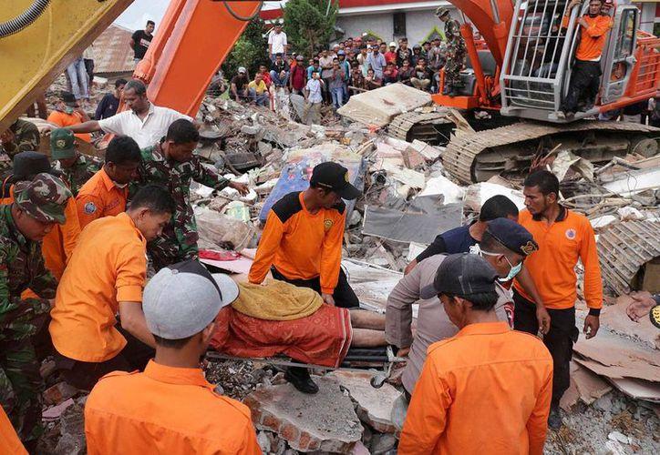 Equipos de rescate evacuan a una víctima de entre los escombros en la provincia de Aceh, Indonesia, afectada por un potente terremoto, el miércoles 7 de diciembre de 2016. (AP/Heri Juanda)
