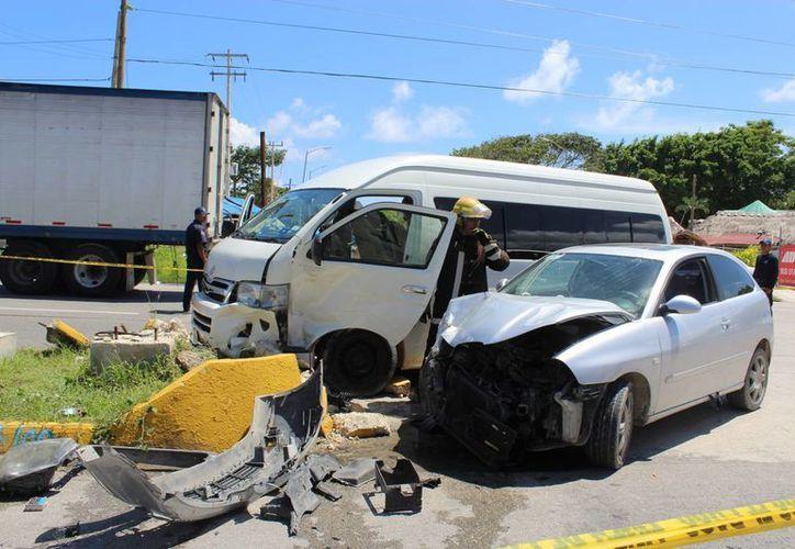La conductora de una camioneta de transporte turístico quedó prensada tras chocar contra un vehículo compacto. (Sara Cauich/SIPSE)