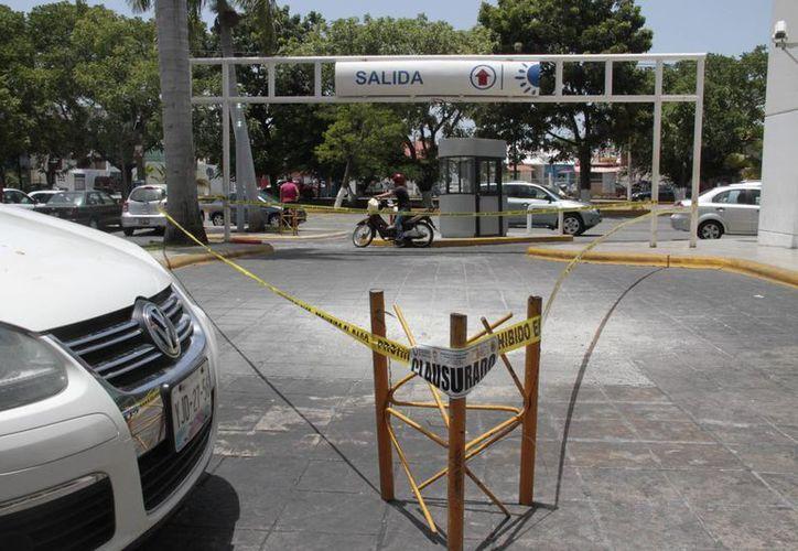 La estructura de un arco metálico con un letrero de estacionamiento se encuentra en mal estado. (Tomás Álvarez/SIPSE)