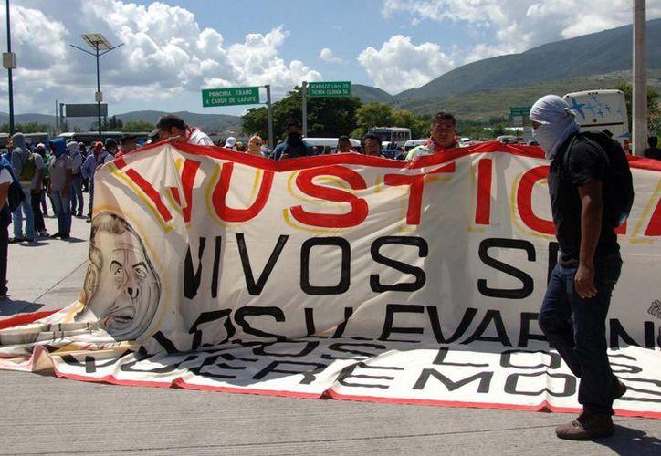 La CNDH indicó que Guerrero vive un momento muy sensible por la inseguridad. En la imagen, estudiantes de la Normal de Ayotzinapa se manifiestan por la desaparición de sus 43 compañeros. (AP)