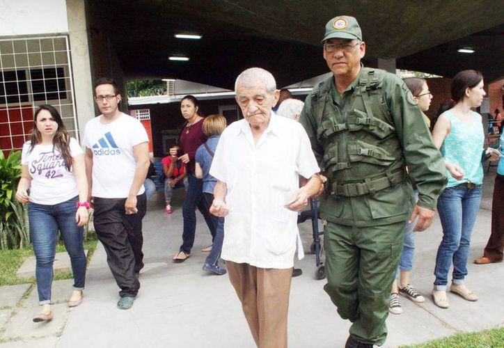Imagen de un militar venezolano al ayudar a caminar a un anciano el día de las elecciones. El ministro de Defensa se negó a colaborar con las intenciones del gobierno del presidente Nicolás Maduro. (Archivo/Notimex)