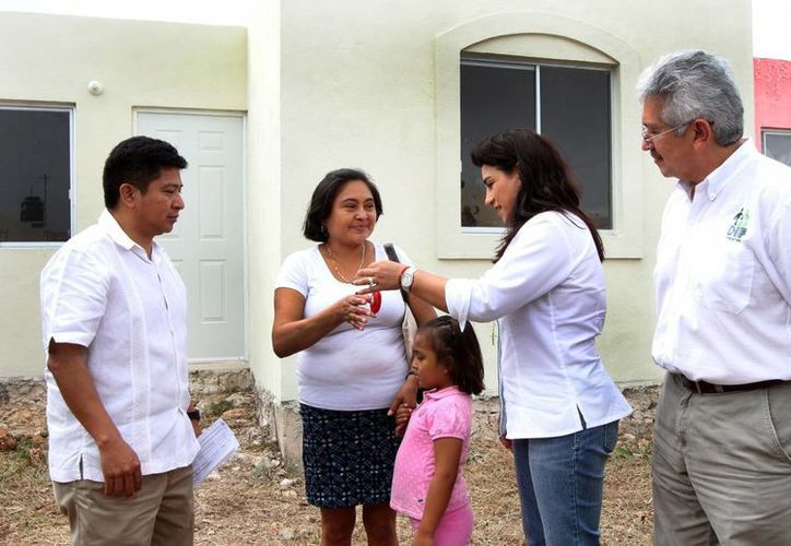 La presidenta del DIF, Sarita Blancarte, entrega las llaves de la casa a una beneficiaria. La acompañan los directores del IVEY y del DIF, César Escobedo y Limber Sosa. (SIPSE)