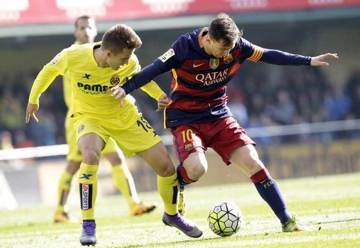 Durante el duelo de este domingo entre Barcelona y Villareal, Lionel Messi lanzó un fogonazo que pegó en una aficionada. Lo fuerte del golpe causó que ésta se desmayara en plena tribuna. (AP)