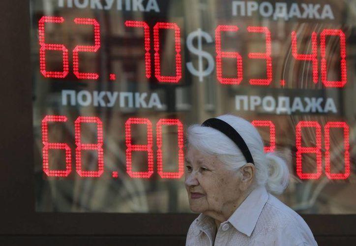 Una anciana camina junto a un panel electrónico que indica la evolución del cambio de divisas en Moscú, Rusia. (Archivo/EFE)
