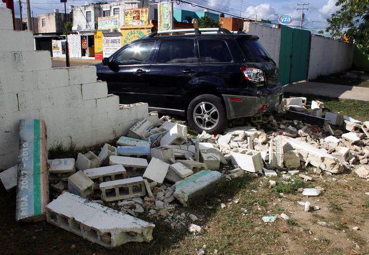 Una mujer con su vehículo salió de un estacionamiento y al no medir bien su distancia tiró la barda de una escuela. (Milenio Novedades)