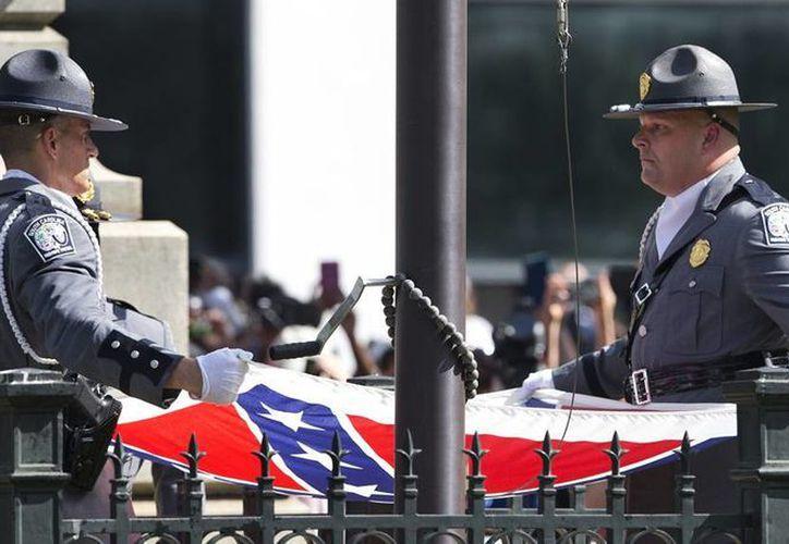 Un guardia de honor de la Patrulla Estatal de Caminos de Carolina del Sur, baja la bandera confederada de terrenos del capitolio estatal en Columbia, Carolina del Sur, luego de una presencia de 54 años en el lugar, este viernes. (Foto AP/John Bazemore)