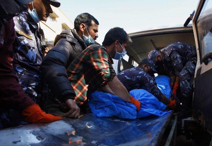 Enfermeros y policías cargan restos humanos hallados en las inmediaciones del lugar donde cayó un avión con 18 pasajeros, en Nepal: todos los ocupantes murieron. (Agencias)
