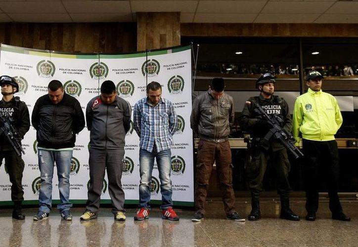 Policías colombianos custodian a cuatro de los seis presuntos responsables del homicidio del agente de la DEA James 'Terry' Watson en Bogotá, Colombia. (EFE)