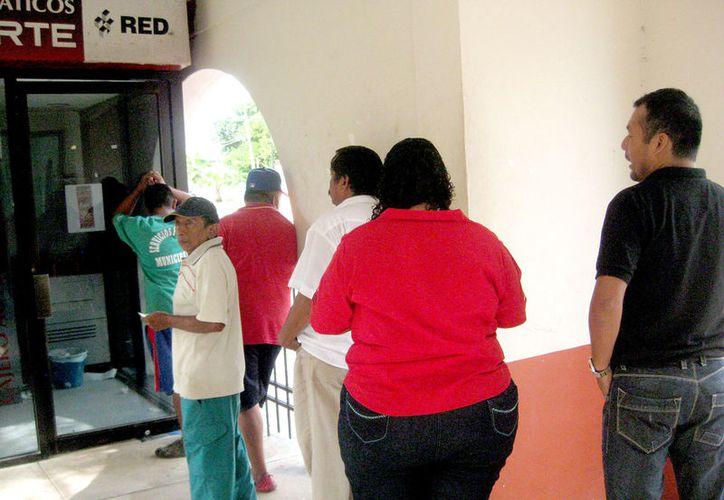 La población se ha quejado porque los cajeros se quedan sin efectivo y porque son insuficientes para atender a todo el público. (Javier Ortiz / SIPSE)