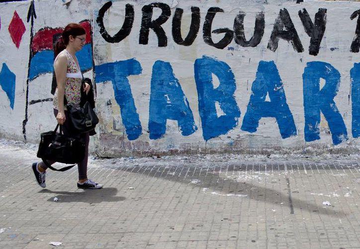 Una mujer pasa junto a un mural promoviendo al candidato presidencial del Frente Amplio, Tabaré Vázquez, un día antes de la segunda vuelta electoral presidencial del país, en Montevideo, Uruguay. (Agencias)
