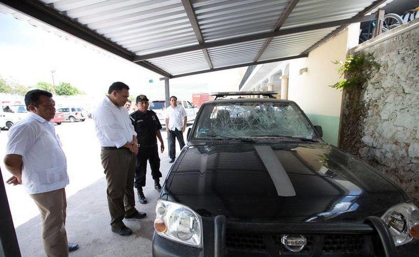 El gobernador Rolando Zapata Bello observa una patrulla de la Policía de Espita, dañada durante un operativo. (Milenio Novedades)