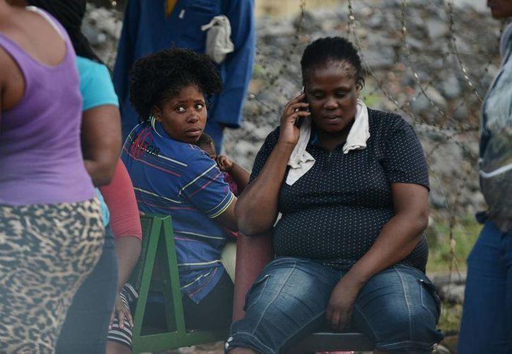 Los preocupados familiares de tres desaparecidos esperan afuera de la entrada a la mina Lily de Vantage Goldfields Limited cerca de Barbeton, Sudáfrica. (Agencias)