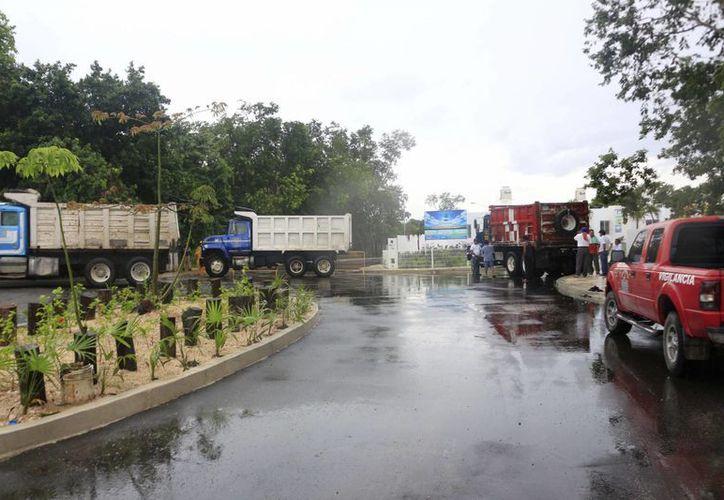A las siete de la mañana de ayer, alrededor de ocho volquetes cerraron el acceso a las camionetas propiedad de la constructora que realiza los trabajos finales del mencionado fraccionamiento. (Harold Alcocer/SIPSE)