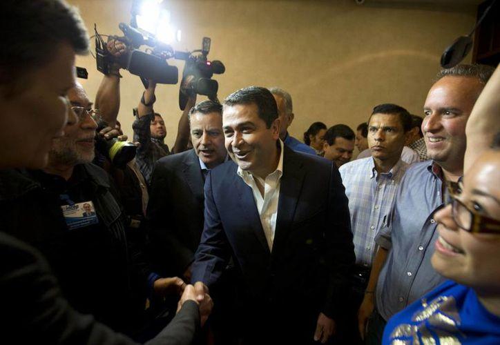 El proceso electoral en el que al parecer Orlando Hernández (al centro) ha resultado ganador, ha sido calificado como limpio por observadores electorales. (Agencias)