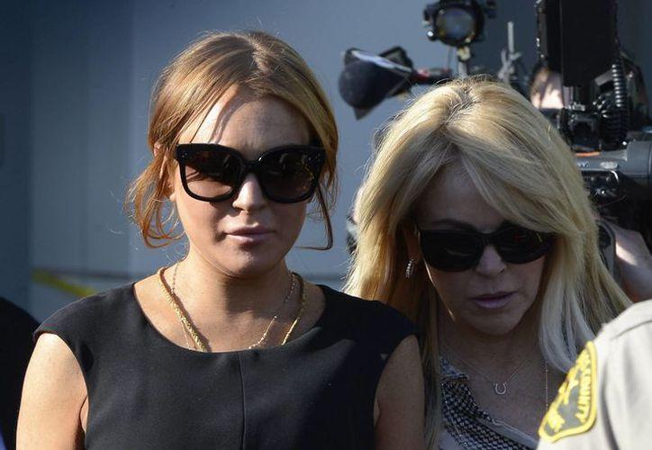 Al parecer, Lindsay Lohan (i) escribió un diario durante la rehabilitación a la que fue sometida el año pasado, el cual le dio la idea de escribir sobre su ajetreada vida. (EFE/Archivo)