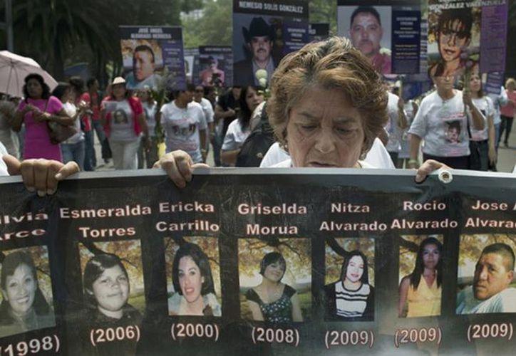 Una mujer lleva una pancarta con fotografías de personas desaparecidas durante una marcha de las madres de desaparecidos en México D.F. en el 2012. (hrw.org)