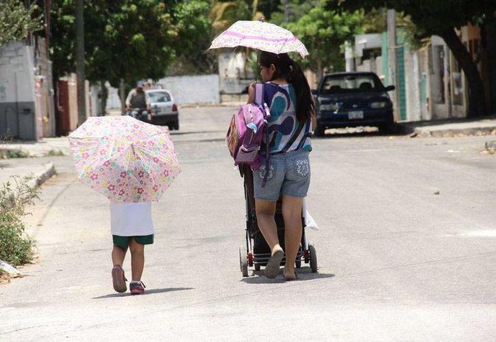 Saque la sombrilla, no sólo para 'evitar' los intensos rayos del sol, sino para protegerse del agua: la probabilidad de que llueva es alta. (Jorge Acosta/Milenio Novedades)