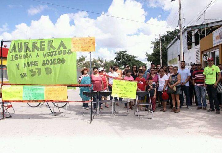 Los vecinos del lugar se manifestaron con pancartas y el cierre de la calle en contra de la apertura de una salida para vehículos pesados en una calle de la Pedregales de Tanlum. (Jorge Acosta/SIPSE)