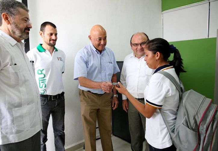 Reunión entre los representantes de la DTEY y la Uady. Imagen del momento que le entregan una credencial de descuento a una alumna. (Milenio Novedades)