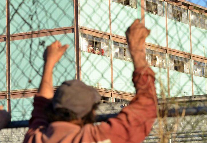 Un hombre se aferra a una cerca que rodea el penal de Topo Chico, donde fallecieron 49 personas durante una riña entre reos. (Agencias)