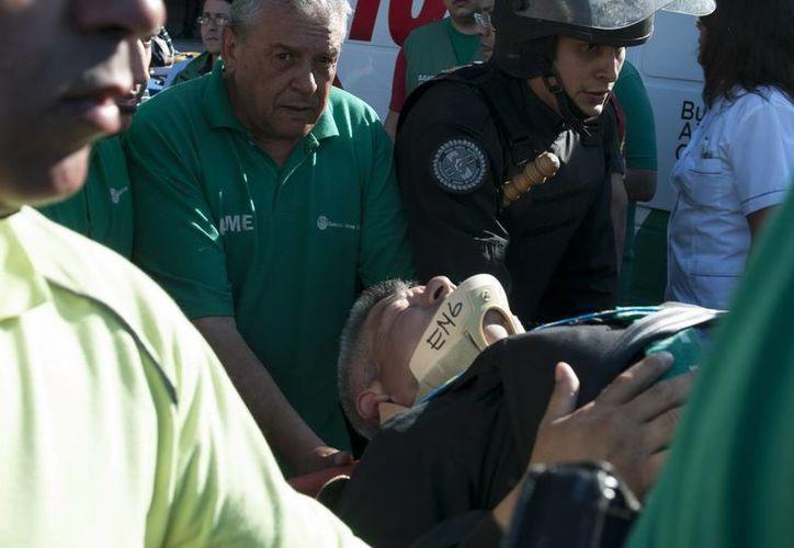 Rescatistas trasladan a un herido tras el accidente de tren en la estación de Once en Buenos Aires. (EFE)