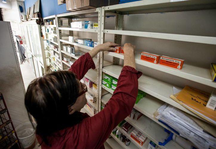 Beatriz Gorostiza, encargada de la farmacia 'San Vicente', arregla los pocos medicamentos que tienen en el establecimiento. (EFE)