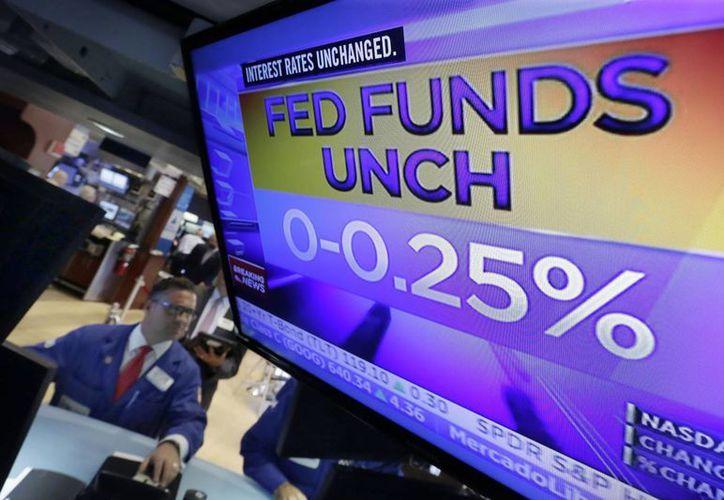Paul Cosentino observa en una pantalla, en la Bolsa de Nueva York, la decisión de la Reserva Federal de mantener la tasa de interés, sin cambios, el 17 de septiembre de 2015. (Foto: AP)