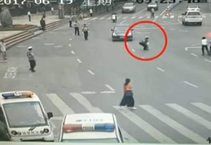 Un policía que se encontraba del otro lado de la avenida, se dio cuenta de la situación y corrió para salvaguardar la vida del niño. (Captura Youtube).