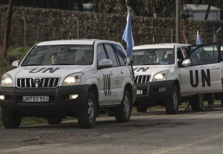 Soldados de la misión de paz de la ONU en los Altos del Golán (UNDOF) esperan para cruzar el paso de Quneitra, en la frontera entre Israel y Siria. (EFE)