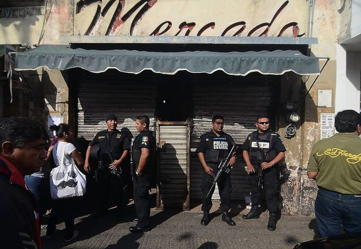 Policías montan guardia frente a Plaza Mercado, en el centro de Mérida. (Cuauhtémoc Moreno/SIPSE)